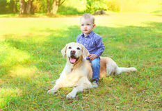 Little boy child sitting on Golden Retriever dog. On grass royalty free stock images