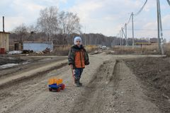 Little boy child with toy walking alone in the village on the road in autumn royalty free stock photo