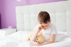 Little boy child waking up at the morning. Hugging his favourite teddy bear Stock Photography