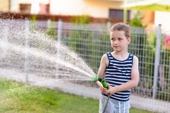 Little boy child watering grass in garden. Royalty Free Stock Images
