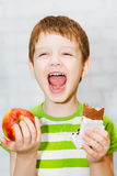 Little boy chooses chocolate or apple on a light background in the st Stock Image