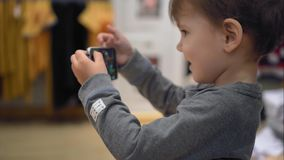 A little boy chooses clothes in the store and takes pictures of her on a smartphone.  stock video