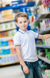 Little boy chooses cosmetics in the shop Stock Photography