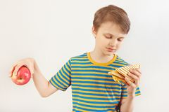 Little boy chooses between fastfood and fruit on white background royalty free stock photos