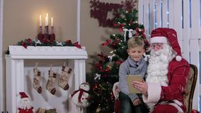 Little Boy Chooses a Gift from Santa on Tablet in