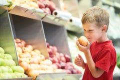 Child boy choosing fruits vegetable shopping. Little boy choosing bio apple food in fruit vegetable shopping store Royalty Free Stock Photography