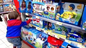 Little boy choosing toys. Portugal, Algarve, Circa March 2018. Little 3 year old boy looking at toys in a Jumbo supermarket Royalty Free Stock Images
