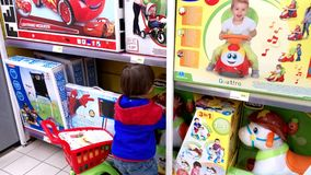 Little boy choosing toys. Portugal, Algarve, Circa March 2018. Little 3 year old boy looking at toys in a Jumbo supermarket Stock Photos