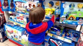 Little boy choosing toys. Portugal, Algarve, Circa March 2018. Little 3 year old boy looking at toys in a Jumbo supermarket Stock Image
