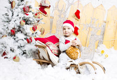 Little boy in Christmas costume sitting on a Christmas tree Royalty Free Stock Image
