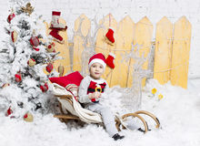Little boy in Christmas costume sitting on a Christmas tree Royalty Free Stock Photos
