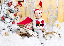 Little boy in Christmas costume sitting on a Christmas tree Stock Photo