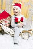 Little boy in Christmas costume sitting on a Christmas tree Royalty Free Stock Photo