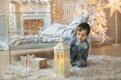 A little Boy and a Christmas lantern. A cute boy looks at a candle in the lantern near the bed at home Royalty Free Stock Image