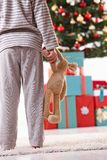 Little boy on christmas morning. Little boy standing with toy handheld in pyjama at christmas tree full of presents on christmas morning Stock Photos