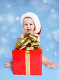 Little boy beside Christmas present. Funny laughing little boy in Santa hat sitting beside red Christmas present Stock Image