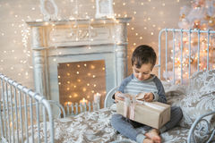 Little boy with Christmas present. Cute little boy in pajamas looking for a gift near the fireplace Stock Images