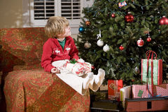 Little boy by Christmas tree with present in lap Stock Photography