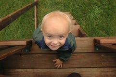 Little Boy in cima alla scaletta Immagine Stock