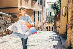 Little boy with city map stay on the old italian street Royalty Free Stock Image