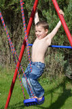 Little boy claims on the swing Stock Images