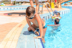 Little boy clambering out of a swimming pool Stock Photos