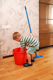 Little boy cleaning the apartment. Little helper. Stock Photo