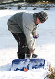 Little boy cleaning ice on pond. Bended little boy in grey clothes and cap cleaning ice from snow on pond in winter Stock Photos