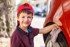 Little boy cleaning red car Stock Image