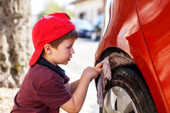 Little boy cleaning wheel Stock Photography