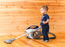 Little boy cleaning wooden floor with hoover royalty free stock photo