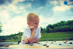 Little boy clever child playing checkers in park Stock Photos
