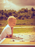 Little boy clever child playing checkers in park Stock Image