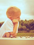 Little boy clever child playing checkers in park Royalty Free Stock Photography