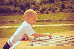 Little boy clever child playing checkers in park Royalty Free Stock Image