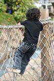 Little boy climbing. Child looking at water on bridge Stock Images