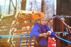 Little boy climbing in adventure activity park Stock Photos
