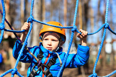 Little boy climbing in adventure activity park Stock Images