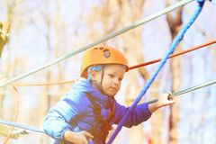 Little boy climbing in adventure activity park Stock Photos