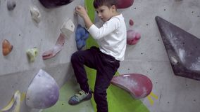 Boy climbing indoor rock wall
