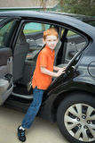 Little boy climbing into backseat of a parked car Stock Image