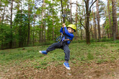 Little boy in climbing gear. In the cable car in jungle park Royalty Free Stock Photography