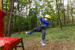Little boy in climbing gear. In the cable car in jungle park Royalty Free Stock Image