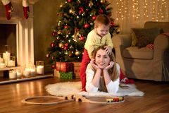 Little boy is climbing his lying mom`s back stock photos