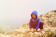 Little boy climbing in mountains Stock Photos