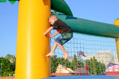 Little boy climbing on a net. Little boy climbing barefoot on a net strung across a colorful inflated plastic jumping castle at a playground Stock Photos