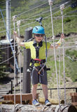 Little boy climbing on an outdoor ropes course. Vertical full length action photo Stock Image