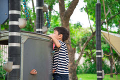 Little boy climbing at playground outdoor activities stock image