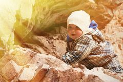 Baby climbing on a rock. Little boy climbing the rock. sunny day royalty free stock photos