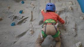 Little boy climbing a rock wall in a harness indoor. Concept of sport life. Little boy climbing a rock wall indoor. Concept of sport life stock footage